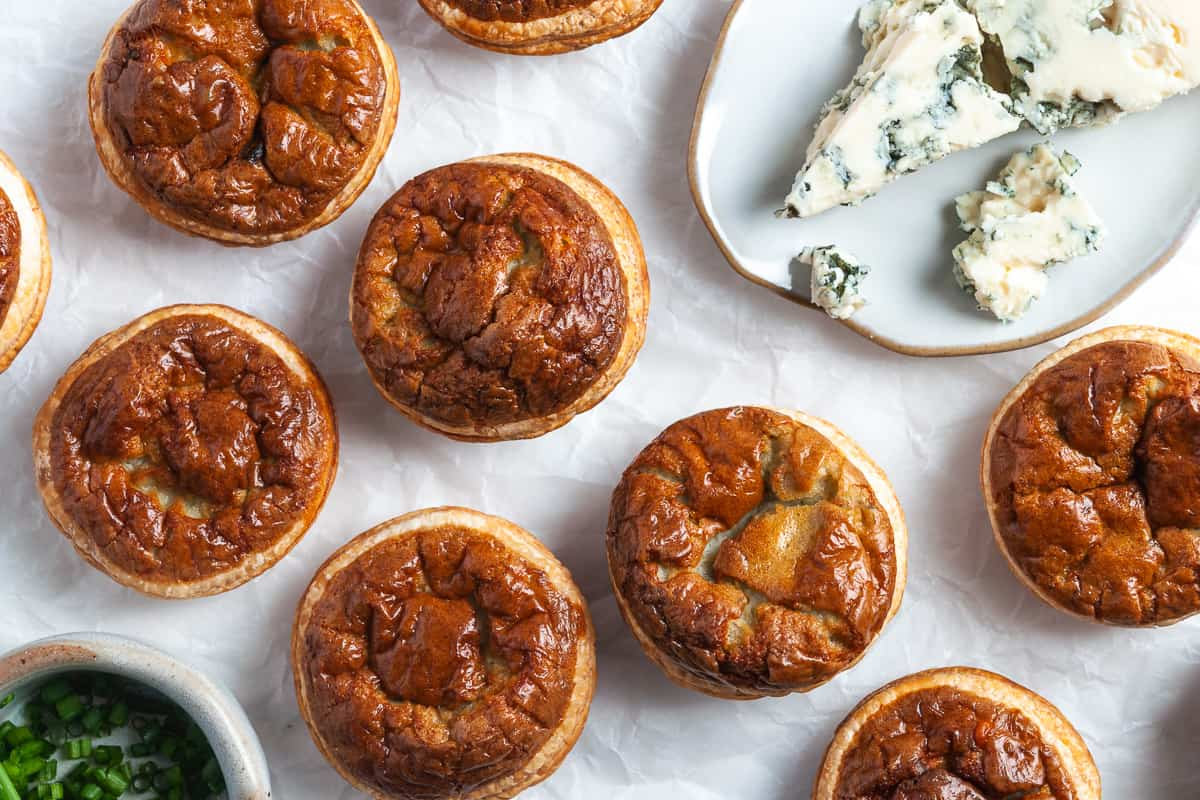 Overhead shot of cooked tartlets with a plate of blue cheese on the side.