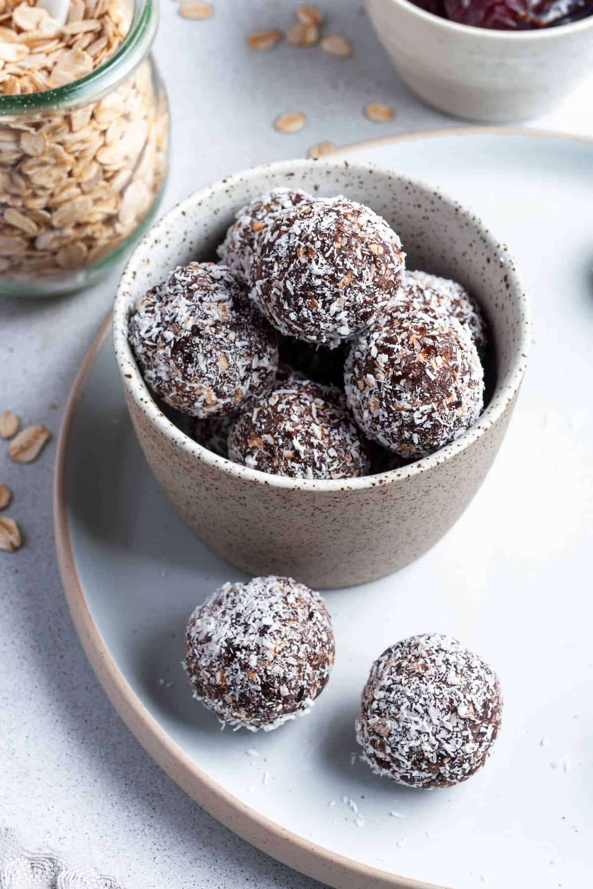 Bowl of bliss balls, sitting on a plate with some bliss balls around the edge, and a jar of oats on the side.