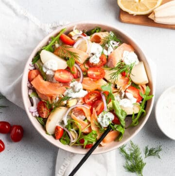 Overhead shot of salad in a round bowl, with a black serving spoon.