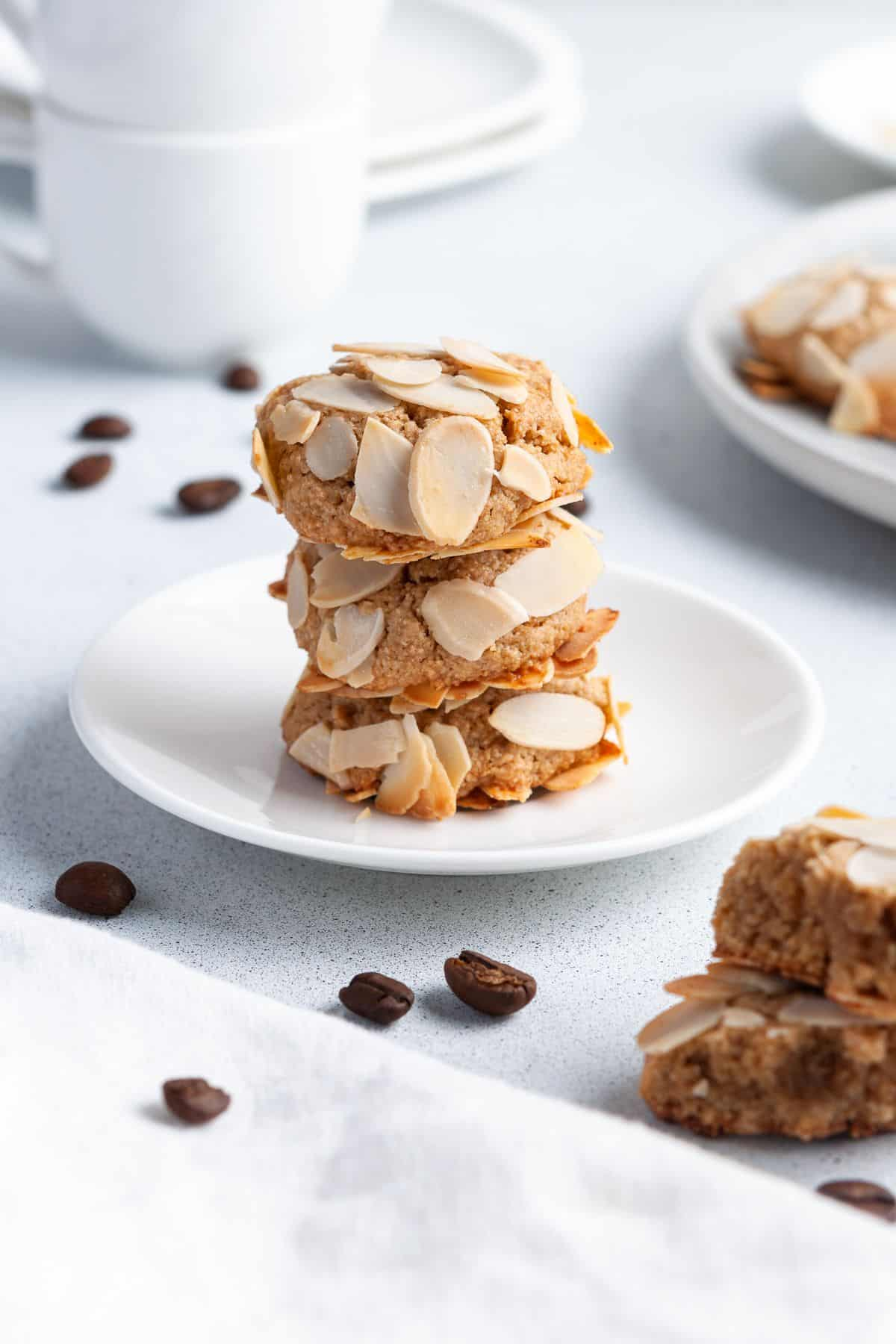 Stack of three cookies sitting on a small round white plate, with some coffee beans around the edge.