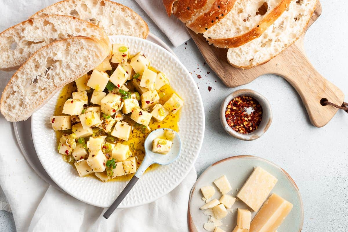 Overhead shot of round white dish of Parmesan, with a spoon scooping some of the cheese out, and some slices of bread and a dish of chilli flakes around the edge.