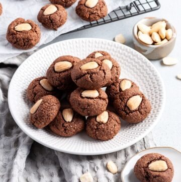 Plate of cookies, sitting on a tea towel, with some almonds in the background.