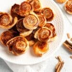 Round white plate of pinwheels, sitting on a white cloth, with some cinnamon sticks around the edge.