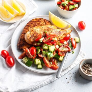 Shot of chicken and salad on a plate, with a wedge of lemon on the side and a fork.