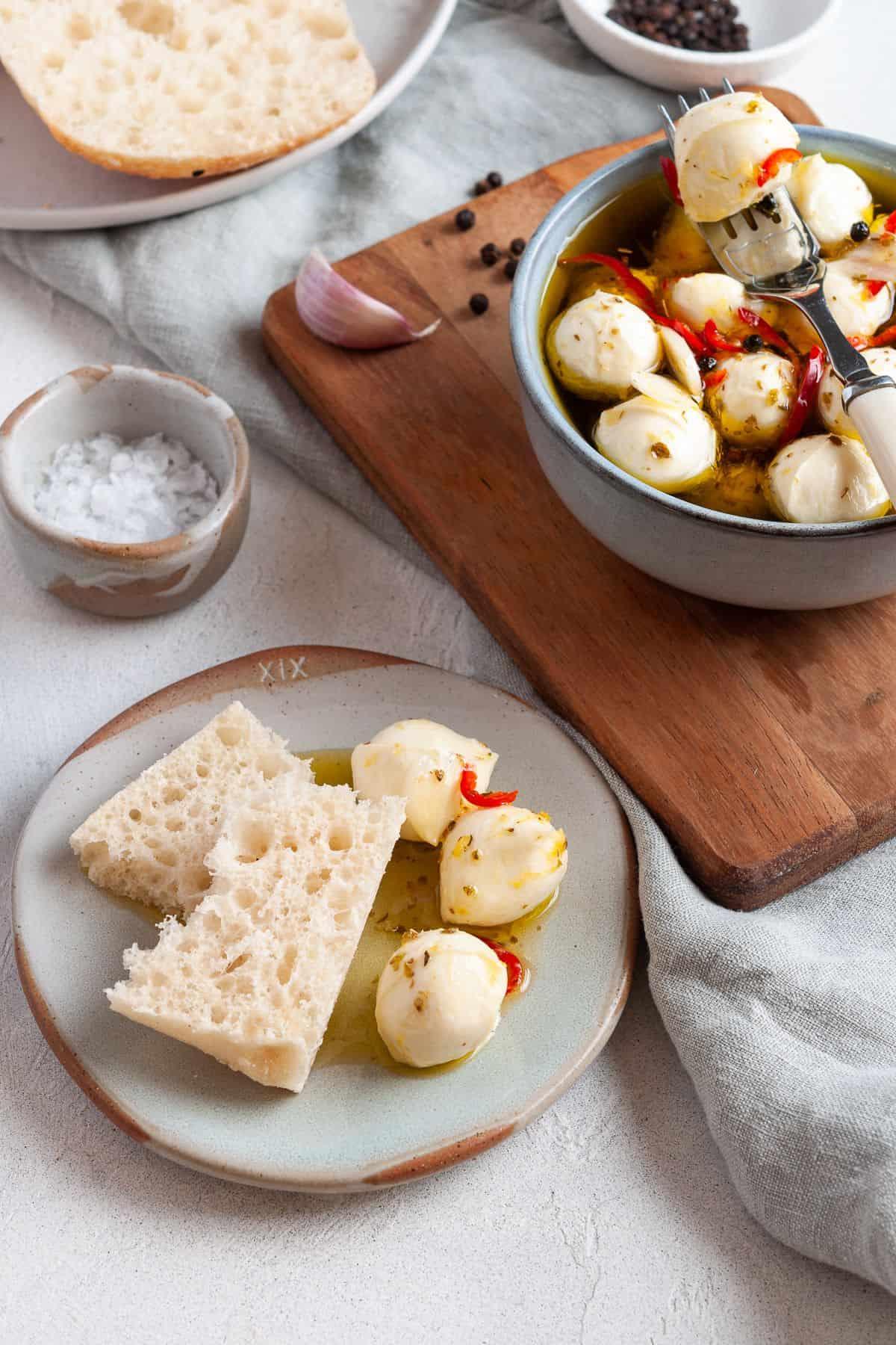 Serve of mozzarella balls on plate with some bread.
