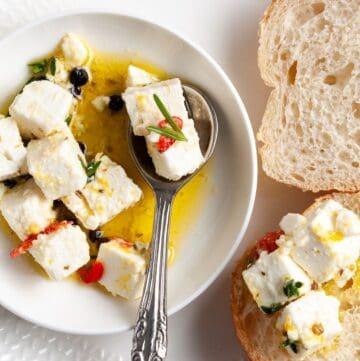 Up close shot of dish of feta, with spoon in it, and some slices of bread around the edge.