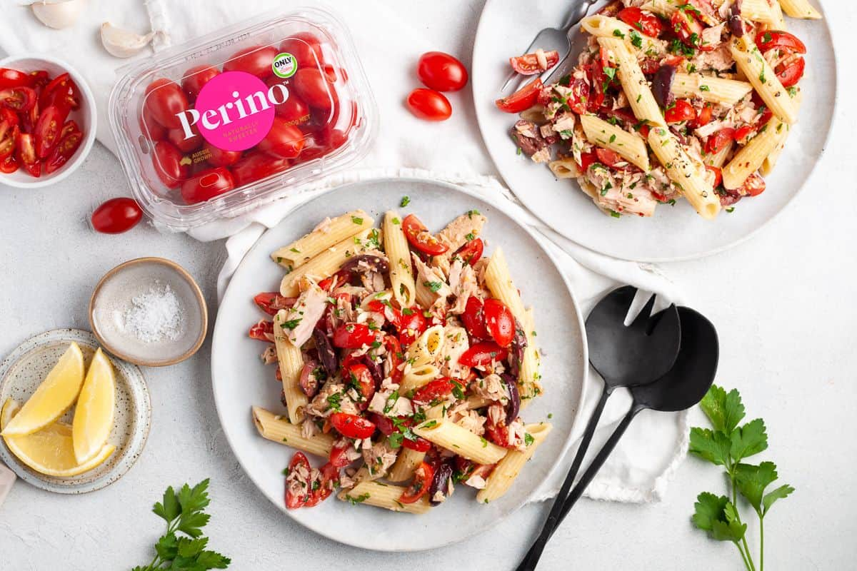 Two plates of pasta salad, with a tub of Perino tomatoes on the side and some lemon wedges and a dish of salt on the edge.