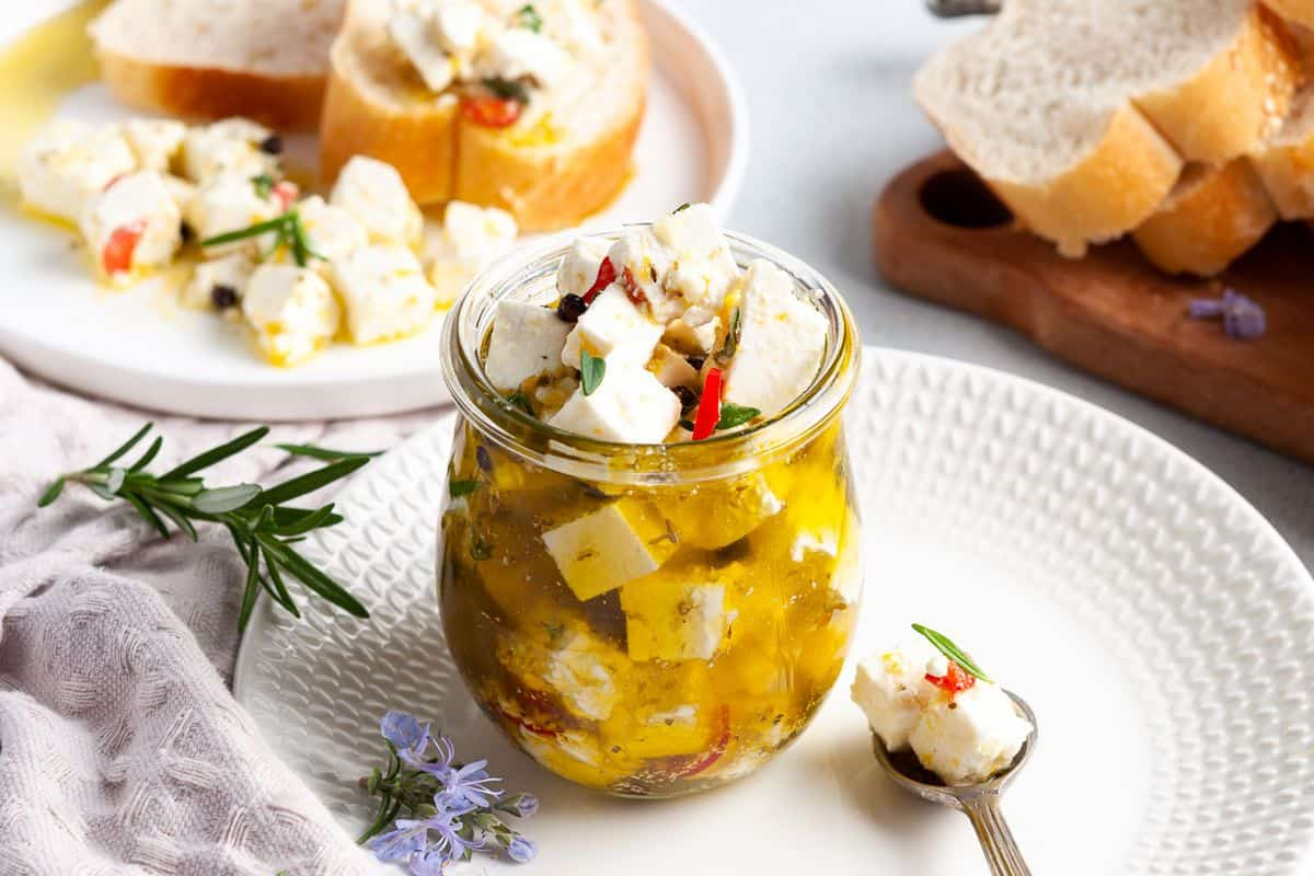 Jar of feta, sitting on a white plate, with a spoon on the edge and some slices of bread in the background.