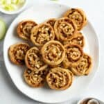 Pinwheels sitting on a round white plate.