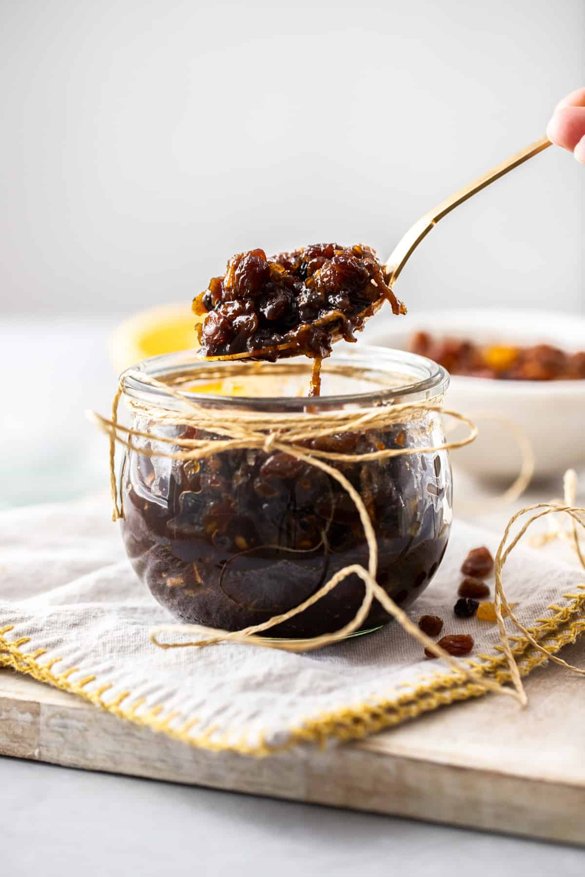 Spoon with fruit mince above jar.