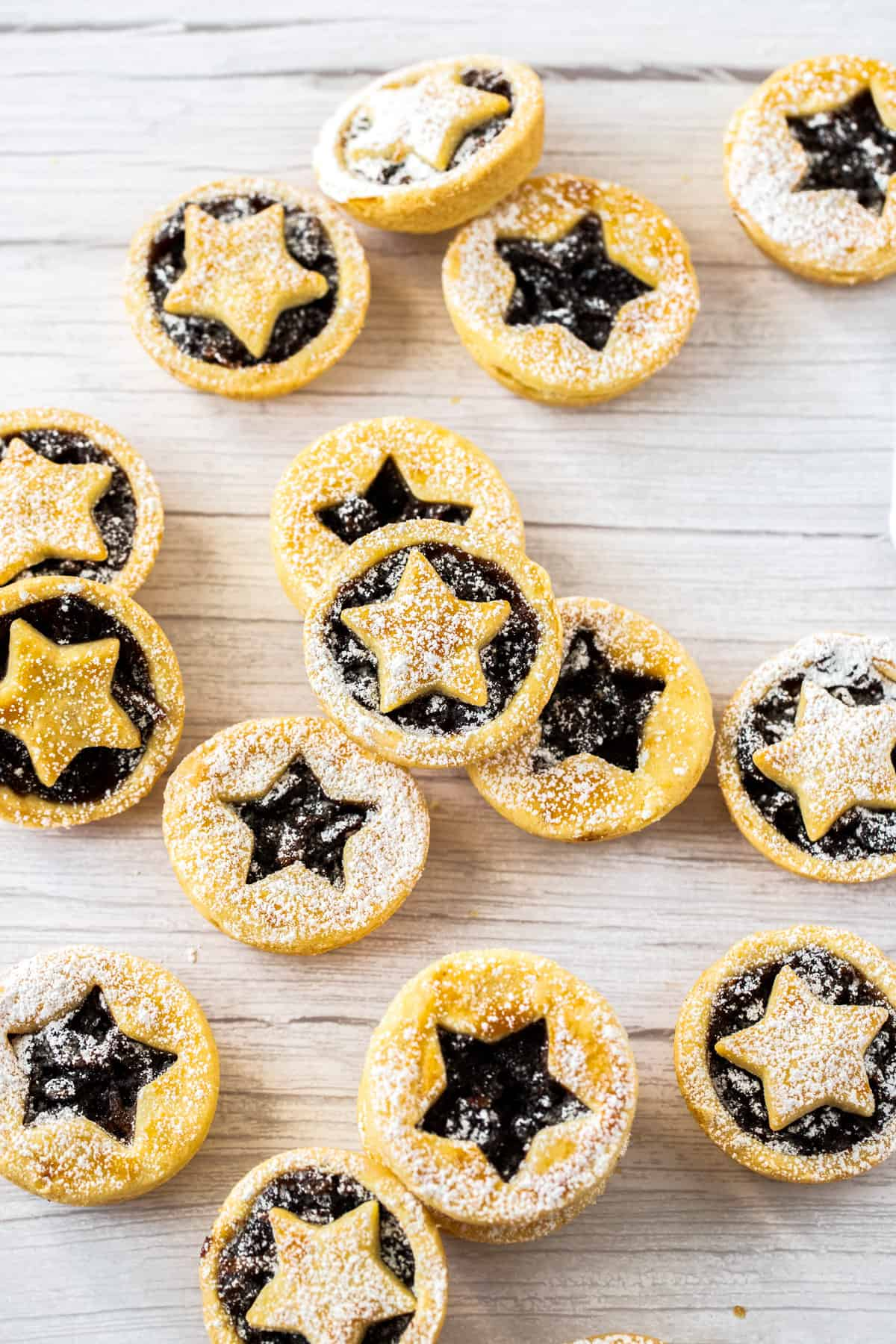 Mince pies dusted with icing sugar on a bench.