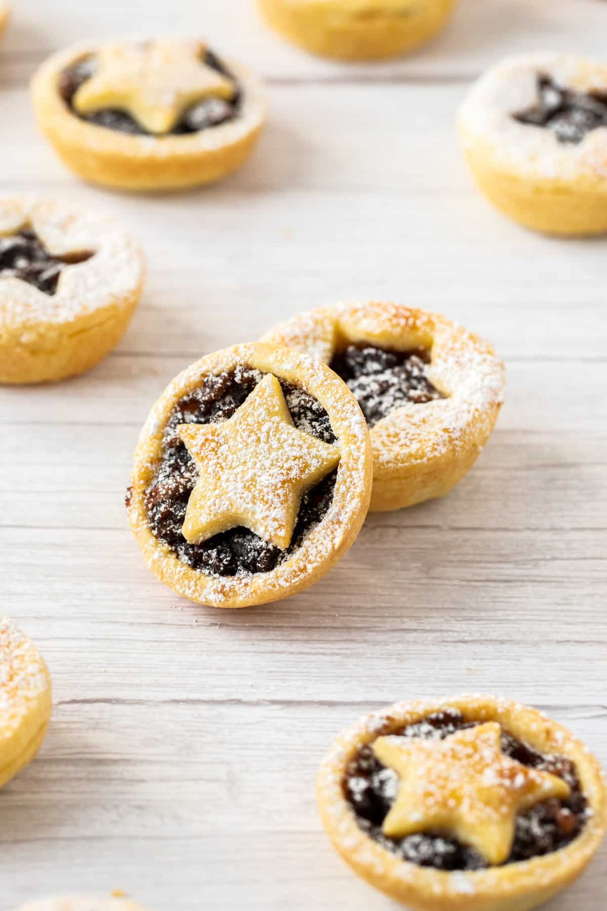 Up close shot of mince pies sitting on a bench.