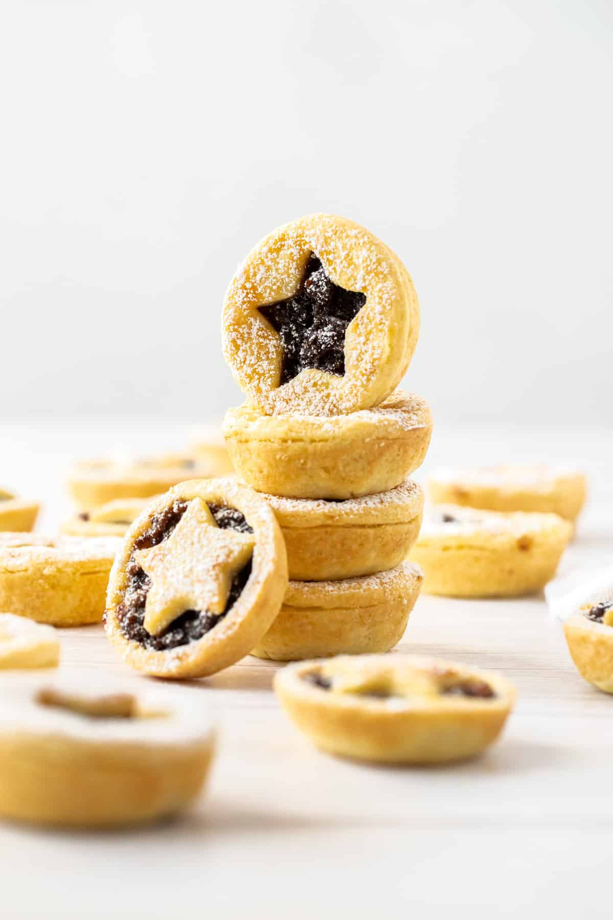 Stack of fruit mince pies, with some more pies around the edge.